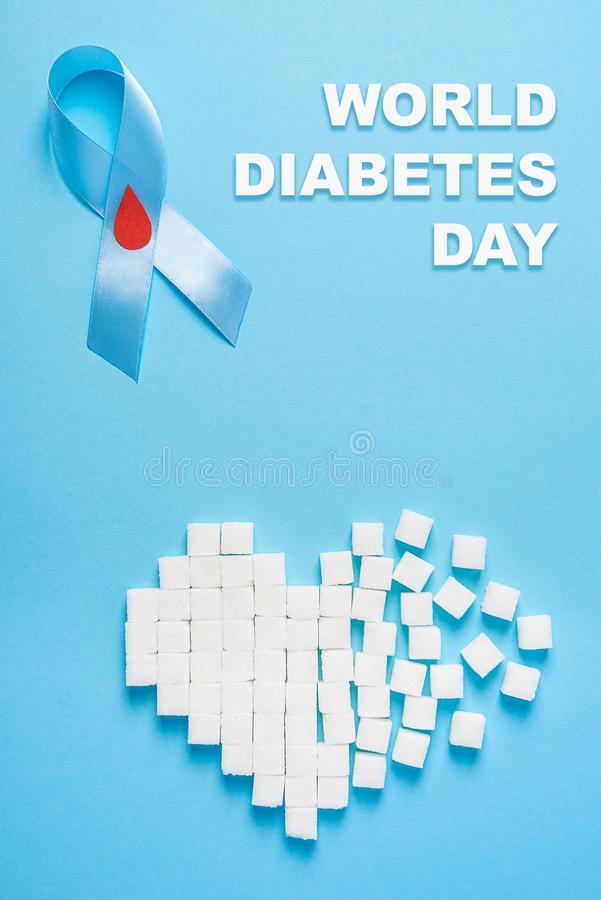 Inscription world diabetes day, blue ribbon awareness with red blood drop, broken heart of sugar cubes, blue background stock image