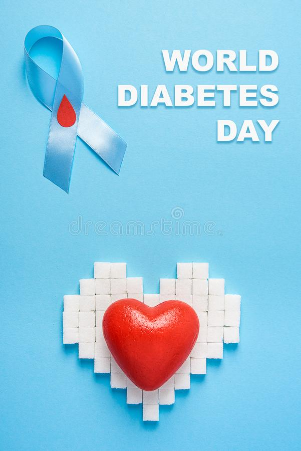 Inscription world diabetes day, blue ribbon awareness with red blood drop, broken heart of sugar cubes, blue background stock photos