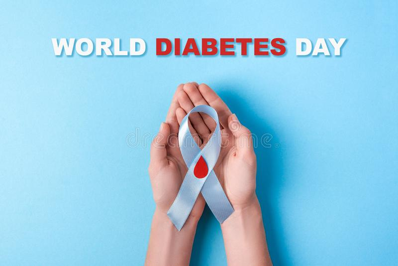 Inscription world diabetes day and blue ribbon awareness with red blood drop in woman hands on a blue background royalty free stock photos