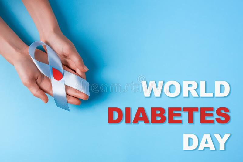 Inscription world diabetes day and blue ribbon awareness with red blood drop in woman hands on a blue background royalty free stock photography
