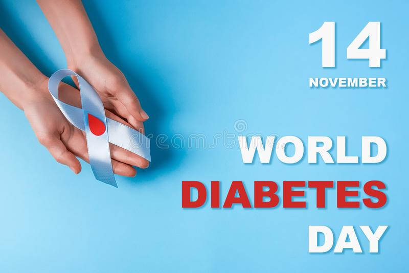 Inscription world diabetes day and blue ribbon awareness with red blood drop in woman hands on a blue background royalty free stock photo