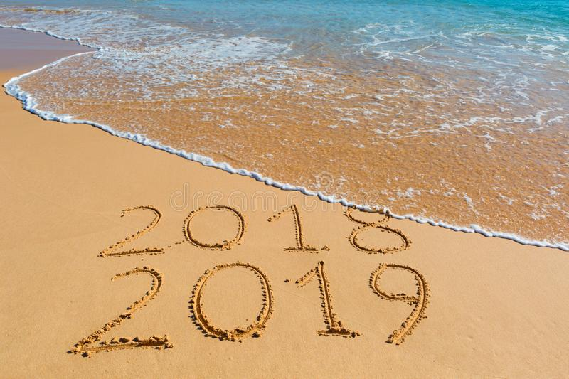 2018 2019 inscription written in the wet yellow beach sand being stock image