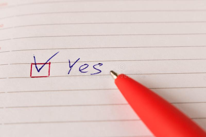 The inscription YES with a tick and a pen on a blank sheet. The concept of consent stock images