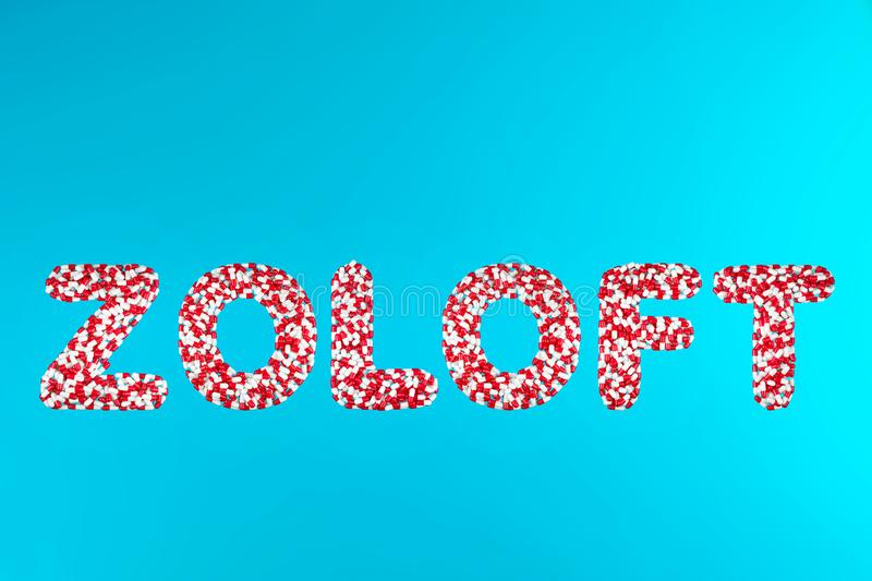Inscription zoloft white and red pills on a blue background royalty free stock photo