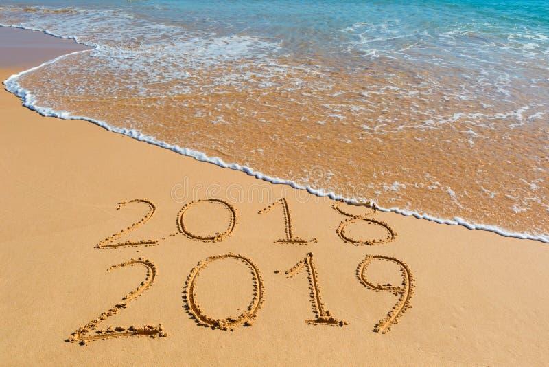 2018 2019 inscriptions écrites dans le sable jaune humide de plage étant image stock