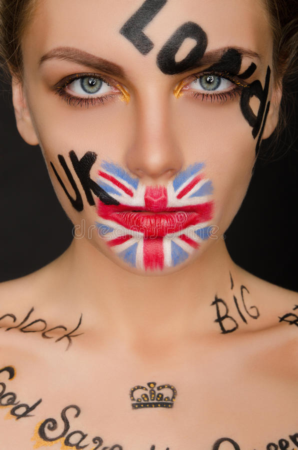 Inscriptions and flag of england on woman`s face royalty free stock photo