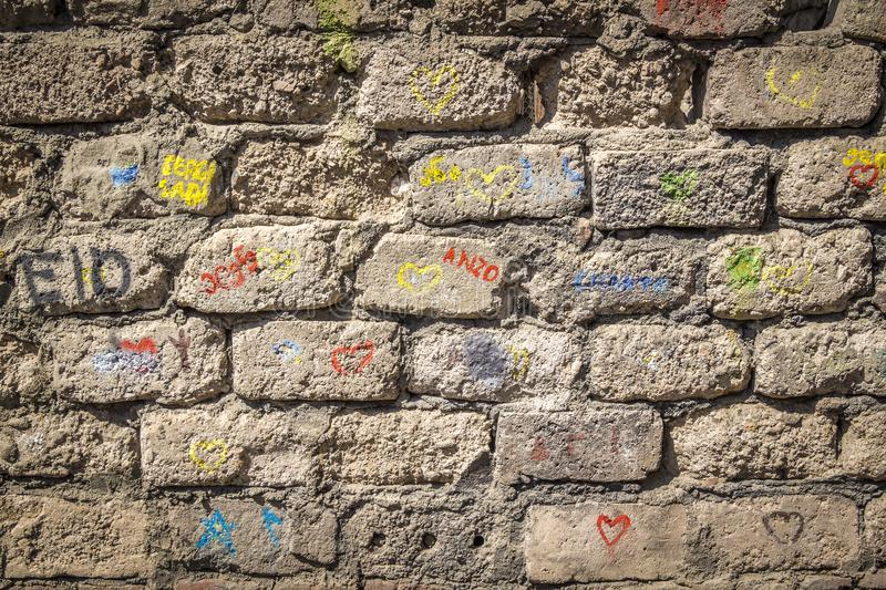Inscriptions on the wall. Multi-colored inscriptions on the old brick wall of the house royalty free stock photos