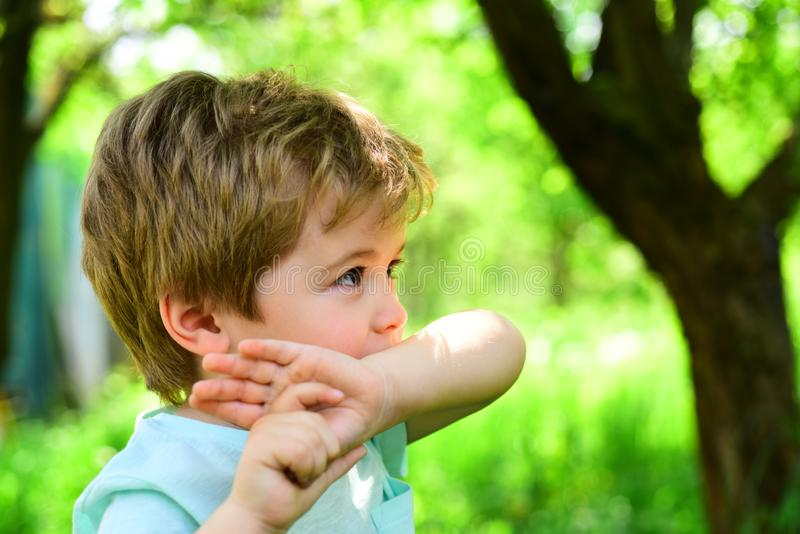 Insect bite, mosquito wound. Remedy for mosquitoes, saliva from bite. Serious look from young boy. Lonely child in park. Sad kid during outdoor walk in forest stock photo