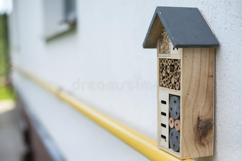 Insect hotel installed on house wall stock photos