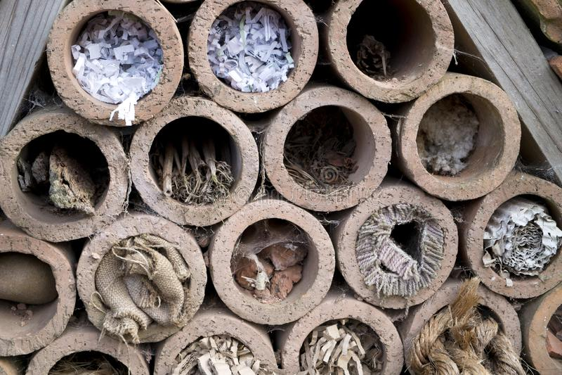 Insect hotel offering nest places. In clay pipes royalty free stock photos