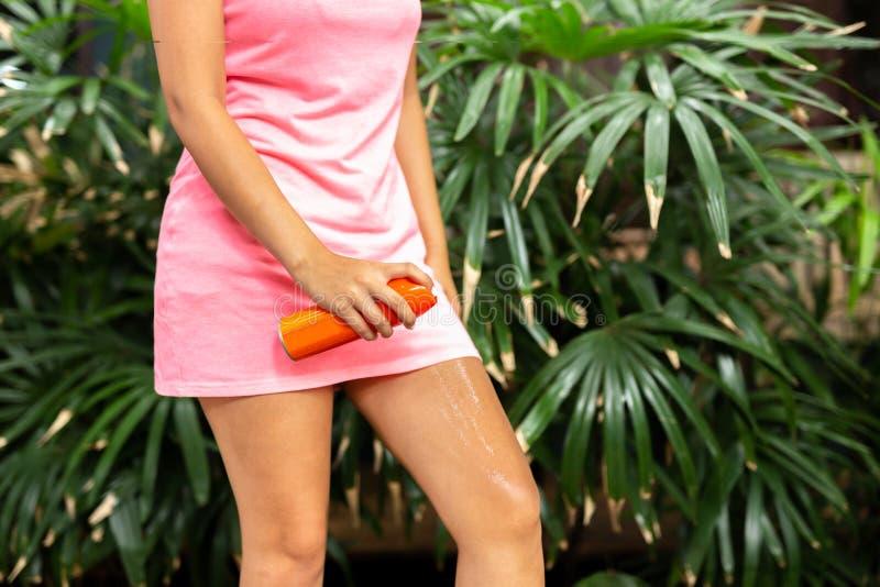 Insectifuge de pulvérisation de moustique de femme sur la jambe extérieure dans la forêt de nature photo stock