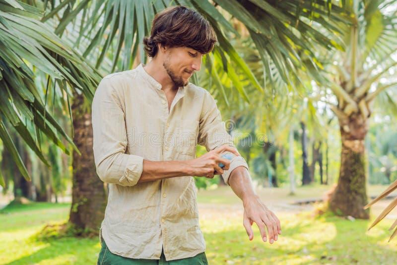 Insectifuge de pulvérisation de moustique de jeune homme dans le forrest, protection d'insecte photographie stock
