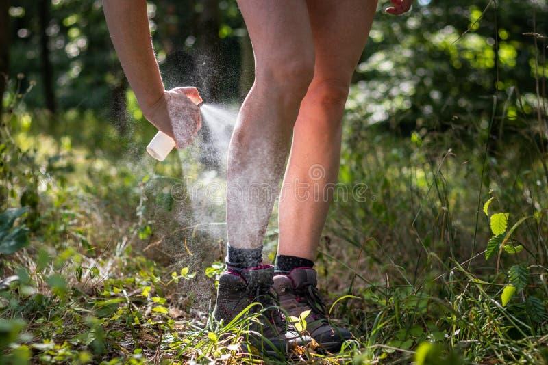 Insectifuge Femme appliquant le produit répulsif de moustique dans la forêt images stock