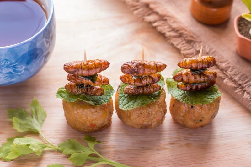Insectos fritos - insecto de madera del gusano curruscante con el rollo del pollo después fotos de archivo