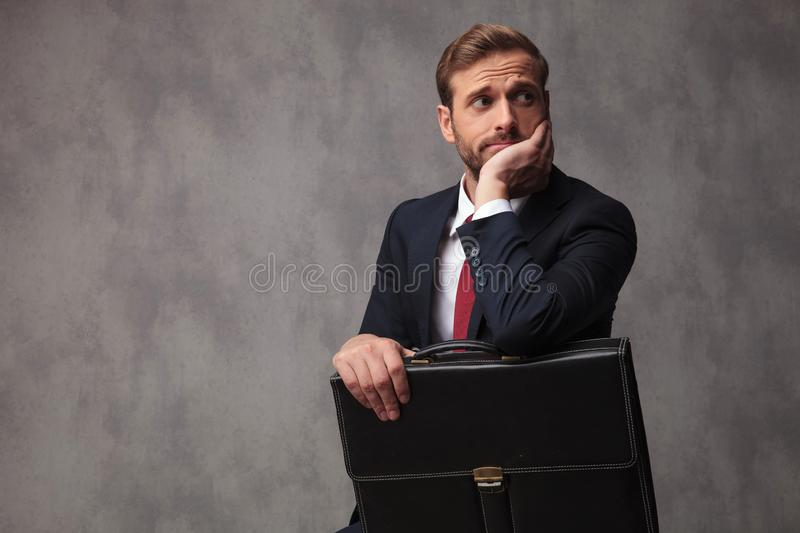 Insecure businessman looks worried and pensive. With chind in his palm, holding his suitcase and looks to side on studio background royalty free stock images