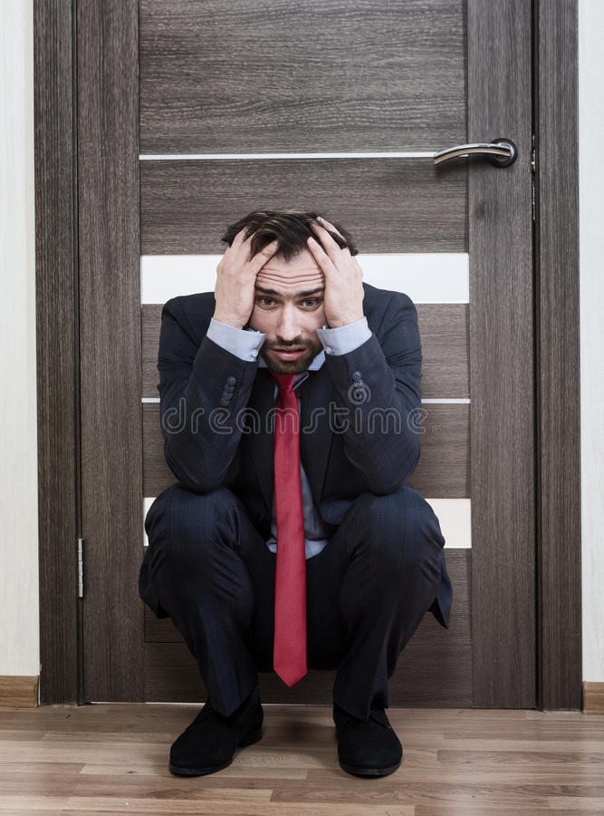 Insecure man waiting for a job interview. Portrait of an insecure man sitting near the office door stock images