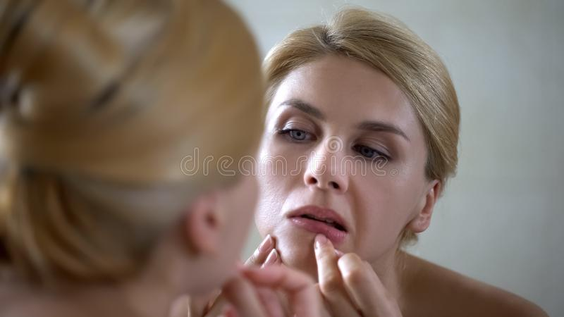Insecure pretty lady popping pimple on skin, scrutinizing her mirror reflection. Stock photo royalty free stock images