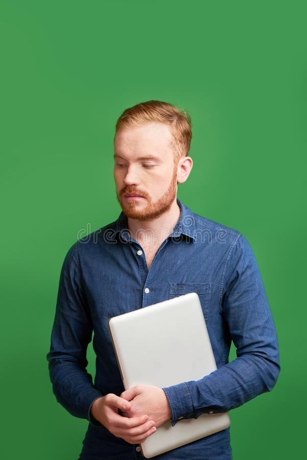 Insecure programmer. Portrait of insecure programmer with laptop, isolated on green stock photos