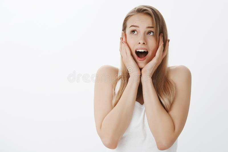 Insecure scared timid girlfriend with fair hair screaming in panic and holding hands on face from fear as looking at royalty free stock photography