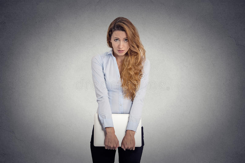 Insecure worried young woman holding laptop feels awkward. Lack of confidence. Insecure worried young woman holding laptop feels awkward isolated grey wall royalty free stock photo