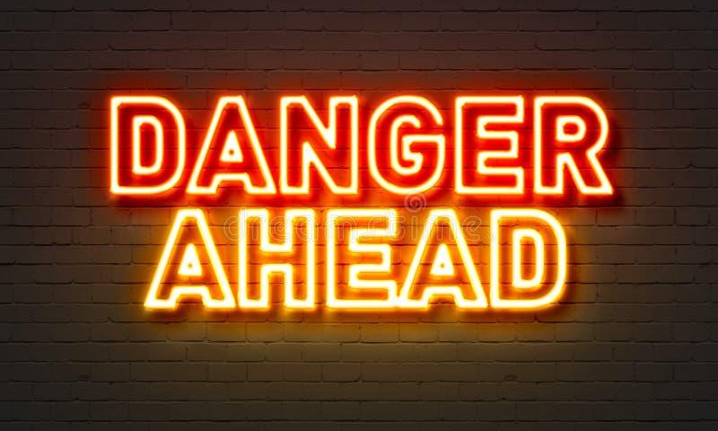 Insegna al neon del pericolo avanti sul fondo del muro di mattoni immagini stock libere da diritti