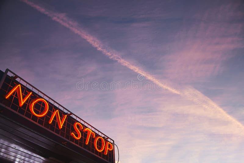 Insegna al neon rossa senza sosta con il cielo di sera nei precedenti con le tracce dell'aeroplano immagine stock