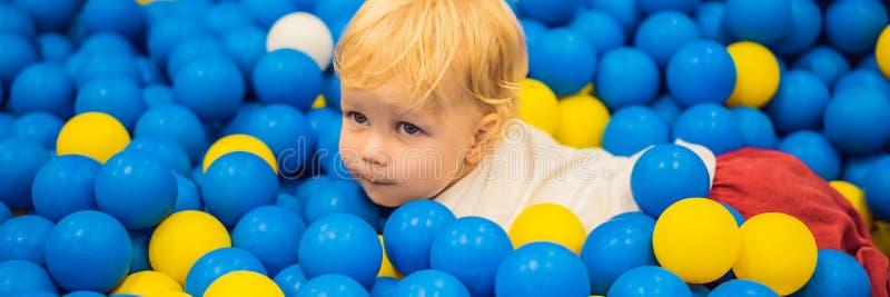 INSEGNA, bambino LUNGO di FORMATO che gioca nel pozzo della palla Giocattoli variopinti per i bambini Asilo o stanza del gioco de fotografia stock