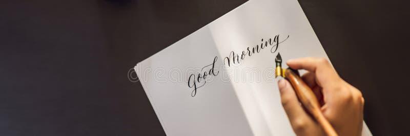 INSEGNA, buongiorno LUNGO di FORMATO Il calligrafo Young Woman scrive la frase su Libro Bianco Iscrivendo ornamentale decorato fotografia stock libera da diritti