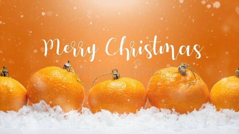 Insegna con i mandarini sotto forma di giocattoli dell'pelliccia-albero sulla neve, con neve di caduta Natale felice o buon anno, fotografia stock libera da diritti