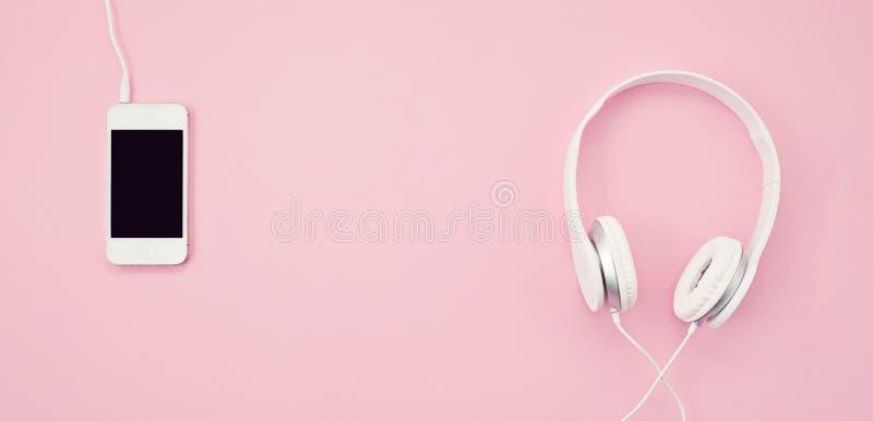 Insegna con il telefono cellulare e le cuffie sopra i precedenti rosa Musica, entertainement, liste musicali radiofoniche online fotografie stock