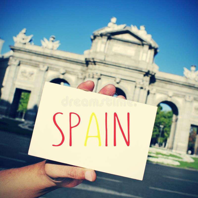 Insegna con la parola Spagna ed il Puerta de Alcala a Madrid dentro immagini stock libere da diritti
