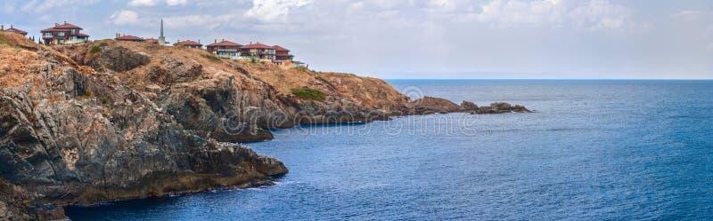 Insegna costiera del paesaggio, panorama - la spiaggia rocciosa con il villaggio di Sozopolis fotografia stock libera da diritti
