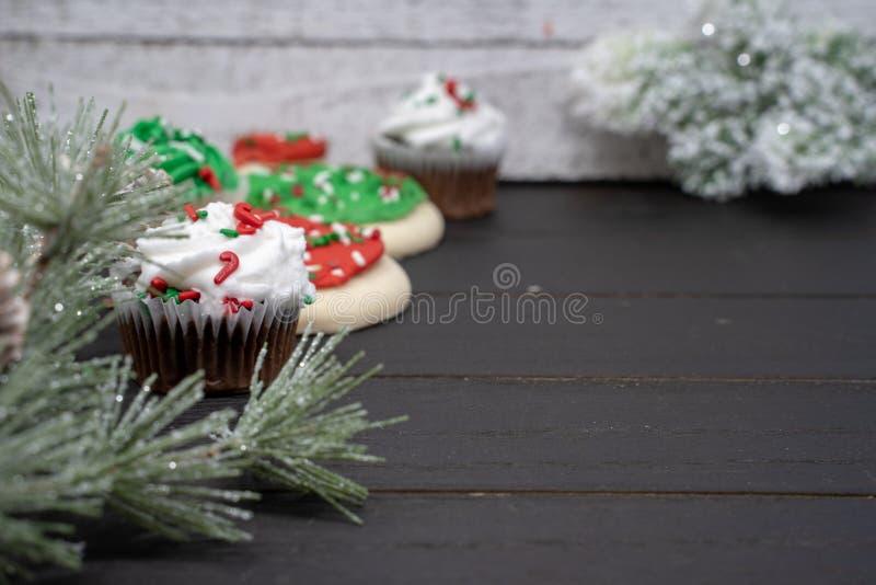 Insegna del fondo del dessert di festa di Natale con i rami luccicanti, i bigné ed i biscotti del pino Fuoco selettivo sul bigné  fotografie stock libere da diritti
