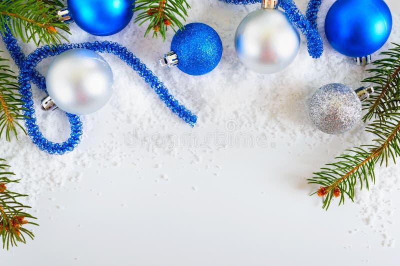 Insegna del nuovo anno con le palle blu e d'argento in neve, rami verdi attillati di Natale su fondo bianco Decorazione di natale fotografie stock libere da diritti