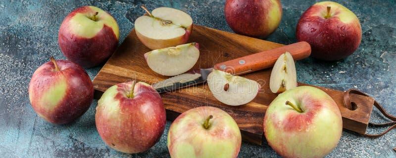 Insegna dell'alimento Mele mature e un coltello su un tagliere di legno Fondo concreto blu immagini stock