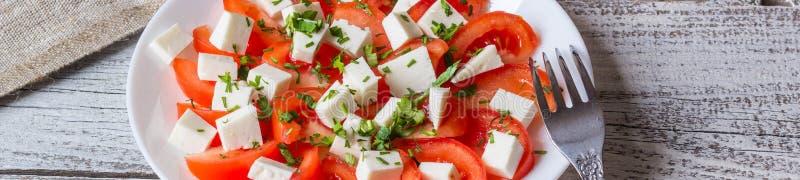 Insegna di insalata fresca con il pomodoro, la mozzarella e le erbe immagini stock