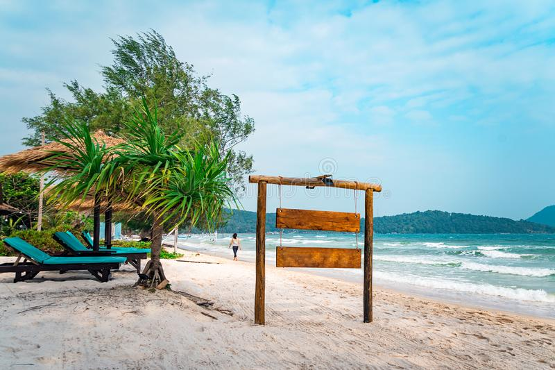 Insegna di legno sulla spiaggia tropicale Un bordo del segno per il nome dell'hotel o della spiaggia su un fondo di bella natura  immagini stock libere da diritti