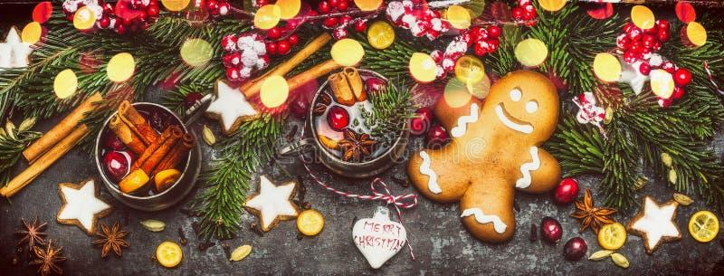 Insegna di Natale con l'uomo di pan di zenzero, i biscotti, il vin brulé, le decorazioni di festa, i rami dell'abete e l'illumina immagini stock