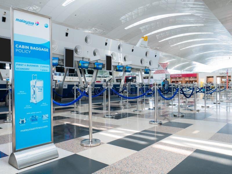 Insegna di politica del bagaglio di cabina di Malaysia Airlines davanti al contatore di registrazione dell'aeroporto fotografie stock
