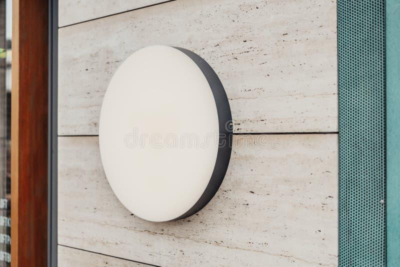 Insegna rotonda in bianco del deposito Svuoti il lightbox del negozio sulla parete immagini stock
