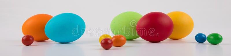 Insegna variopinta delle uova di Pasqua grande e piccolo sull'uovo bianco del fondo, immagine stock libera da diritti