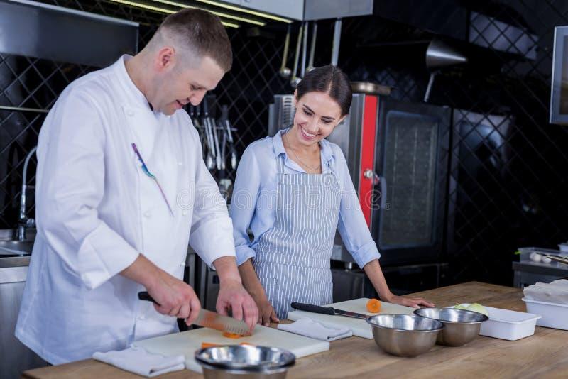 Insegnamento con esperienza del cuoco come cucinare i piatti deliziosi immagine stock