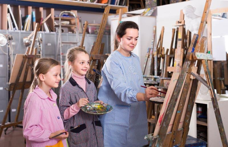 Insegnante abile della donna che mostra le sue abilità durante la classe della pittura immagine stock