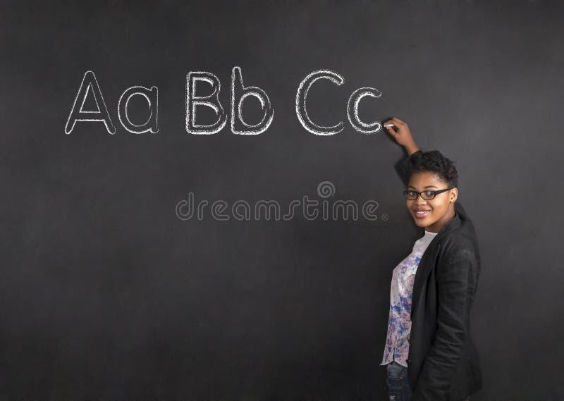 Insegnante afroamericano della donna che scrive ABC sul fondo del bordo del nero del gesso immagine stock