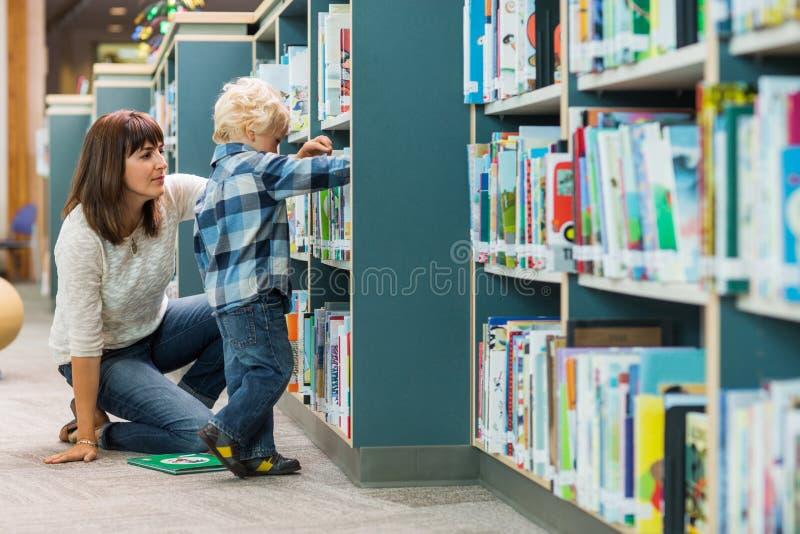 Insegnante Assisting Boy In che seleziona libro a partire fotografia stock libera da diritti