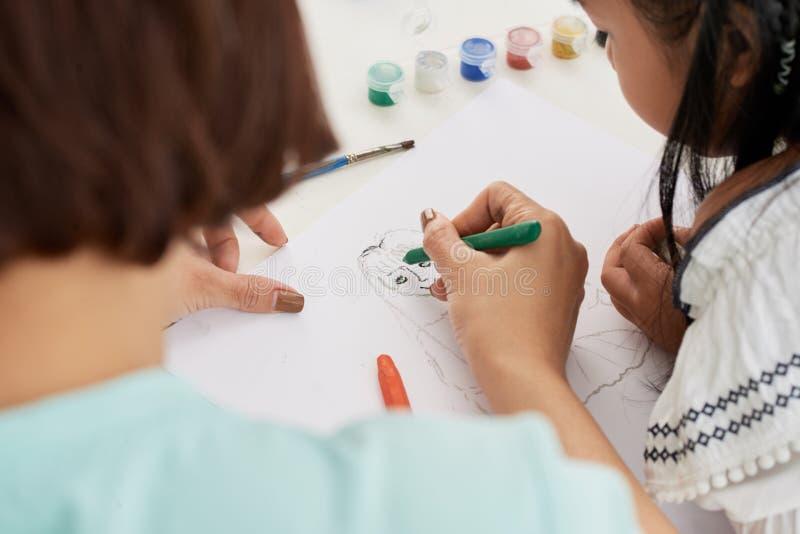 Insegnante che aiuta alla ragazza con pittura immagini stock