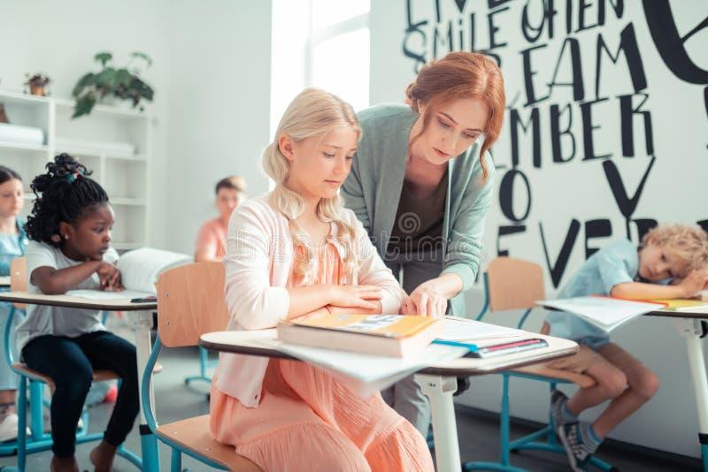 Insegnante che aiuta il suo allievo durante la lezione immagine stock