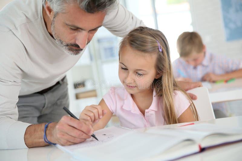 Insegnante che aiuta un allievo della ragazza nella classe immagine stock libera da diritti