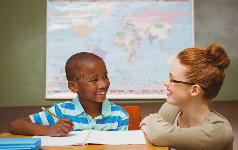 Insegnante che assiste ragazzino con compito in aula immagine stock