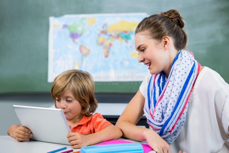 Insegnante che assiste ragazzo che per mezzo della compressa digitale immagini stock libere da diritti